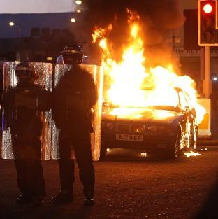 Riot police stand next to a burned out car after loyalist protesters attacked police lines in east Belfast