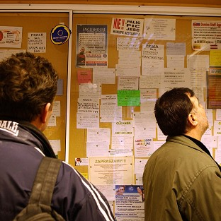 Migrant workers look for a job in a newsagents in London