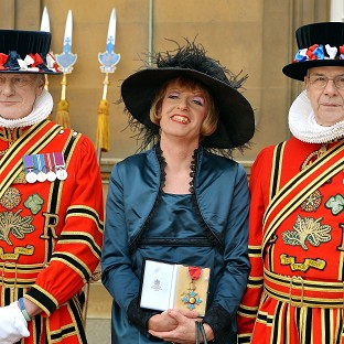 Artist Grayson Perry holds his CBE presented to him by the Prince of Wales during an investiture ceremony at Buckingham Palace