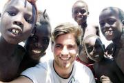 Ben Warrilow is mobbed by children on his visit to Africa